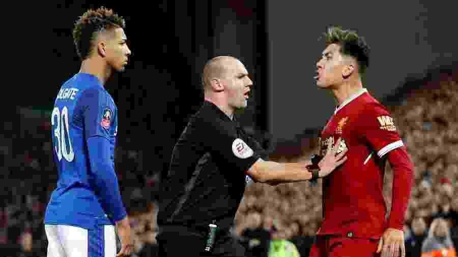 O árbitro  Bobby Madley segura o brasileiro Roberto Firmino, do Liverpool, durante jogo do Campeonato Inglês - Reuters/Carl Recine