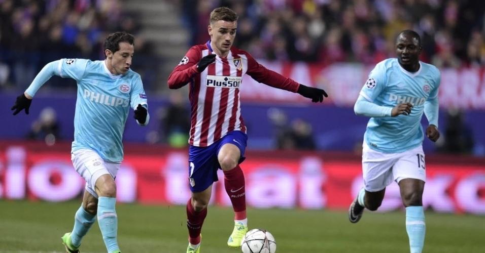 Griezmann, estrela do Atlético de Madri, conduz bola entre dois adversários