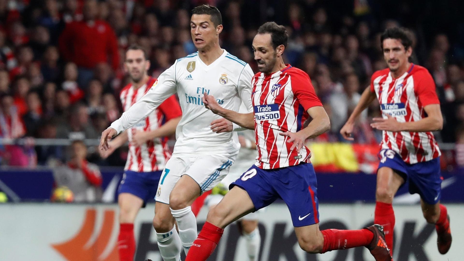 Cristiano Ronaldo tenta ficar com a bola na disputa durante a partida do Real contra o Atlético de Madri