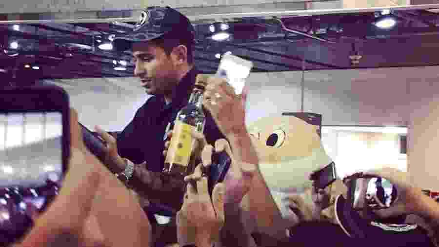 Leandro Carvalho é recepcionado com caçhaça em aeroporto - Reprodução