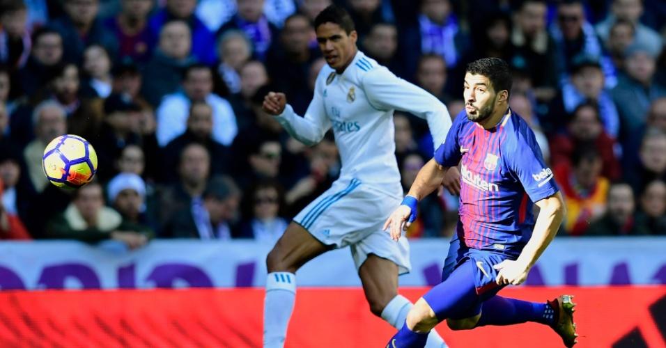 Luis Suárez é observado por Raphael Varane durante clássico entre Real Madrid e Barcelona