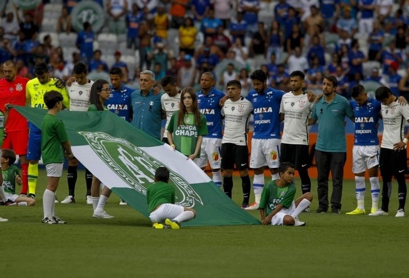 Jogadores de Corinthians e Cruzeiro se abraçam antes do pontapé inicial, enquanto bandeira da Chapecoense é exibida no gramado do Mineirão