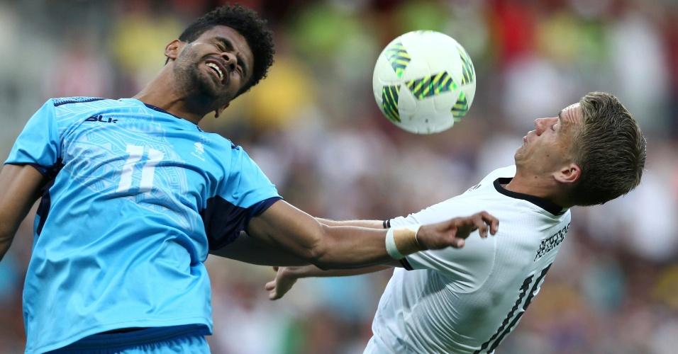Alvin Singh, do Fiji, na jogada dividida com o alemão Nils Petersen