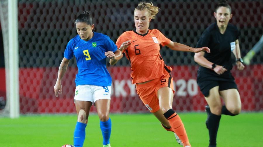 Debinha, do Brasil, disputa bola com Jill Roord, da Holanda, na segunda rodada do futebol feminino nos Jogos Olímpicos - Kohei CHIBAHARA / AFP