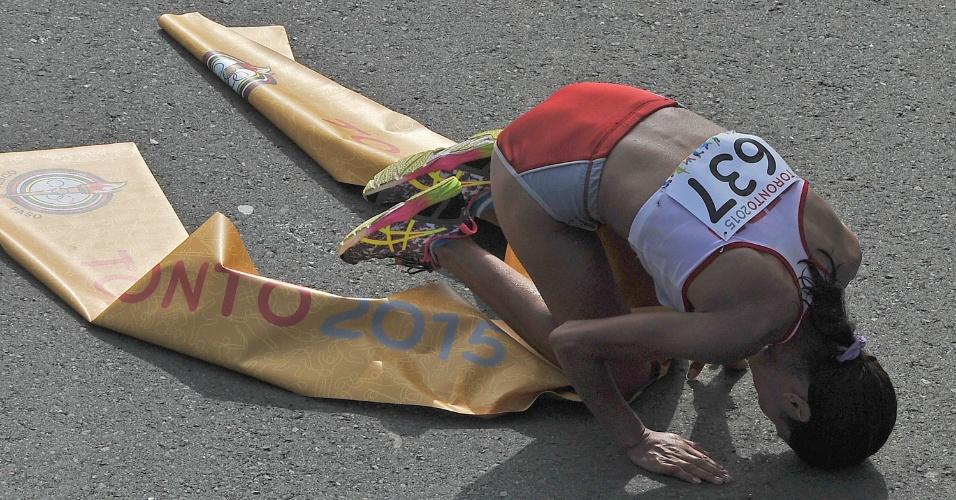 Peruana Gladys Tejeda se ajoelha depois de completar a maratona em primeiro. Brasileira Adriana da Silva ficou com a medalha de prata