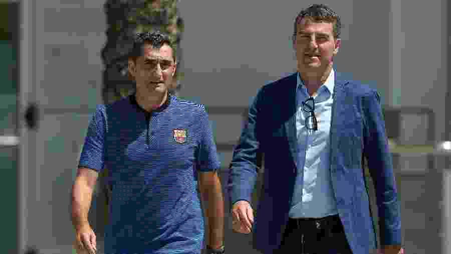 O técnico Ernesto Valverde (esq.) e o dirigente Robert Fernández (dir.) caminham no CT do Barcelona - Lluis Gene/AFP