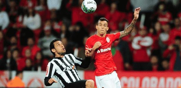 Iago, lateral esquerdo do Inter, disputa bola com Fred em partida contra o Atlético-MG - Ricardo Duarte/Inter - Ricardo Duarte/Inter