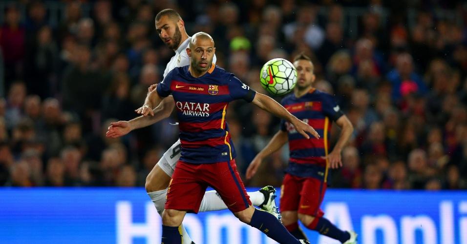 Mascherano tenta proteger a bola da marcação de Benzema no clássico entre Barcelona e Real Madrid pelo Campeonato Espanhol
