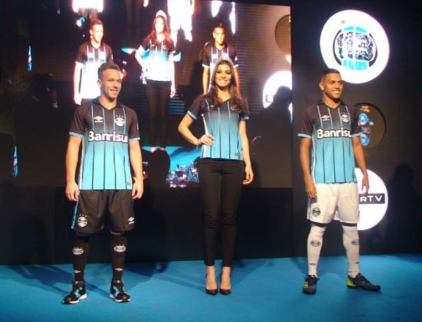 Arthur (e), Letícia Kuhn (c) e Pedro Rocha (d) desfilam nova camisa do Grêmio