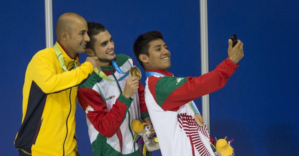 Somos rivais só fora do pódio! O mexicano Jonathan Ruvalcaba (bronze) tira a foto com o compatriota Ivan Garcia (ouro) e o colombiano Victor Ortega (prata) no pódio da prova dos 10 metros dos saltos ornamentais