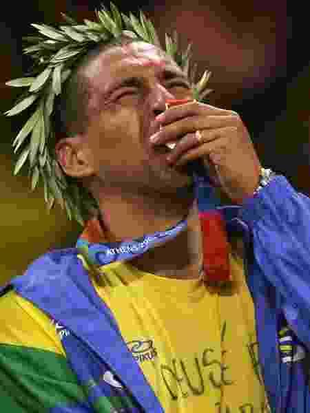 Sérgio Escadinha, líbero da seleção brasileira de vôlei, beija a medalha de ouro conquista nas Olimpíadas de Atenas, em 2004 - Adam Pretty/Getty Images