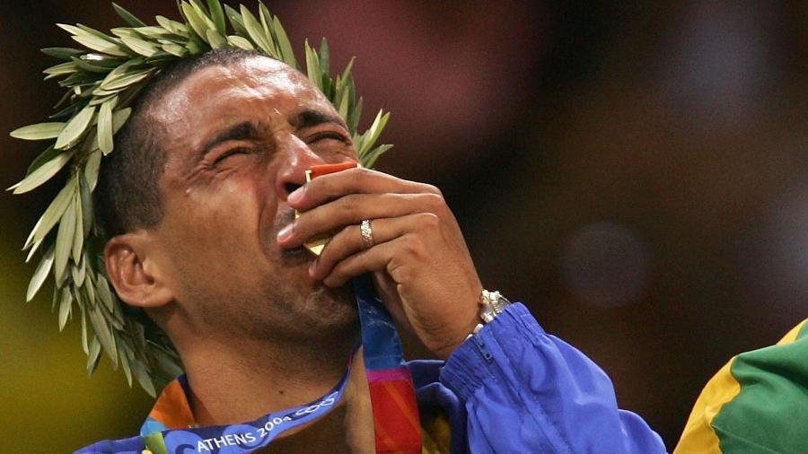 Sérgio Escadinha, líbero da seleção brasileira de vôlei, beija a medalha de ouro conquista na Olimpíada de Atenas, em 2004 - Adam Pretty/Getty Images