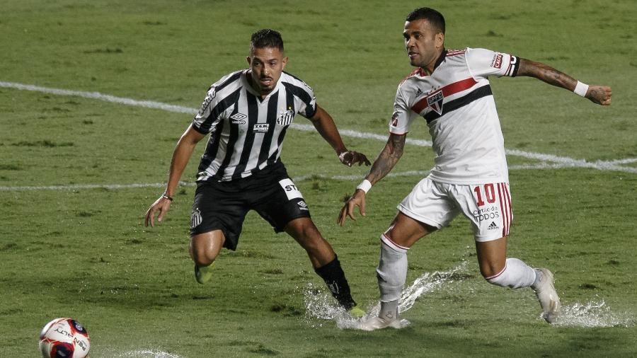 Jean Mota, Santos, e Daniel Alves, São Paulo, disputam a bola durante o clássico -  Ettore Chiereguini/AGIF