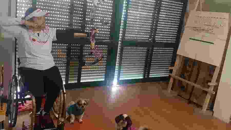 Jane Karla treina tiro com arco na sala do seu apartamento em Lisboa - Arquivo Pessoal