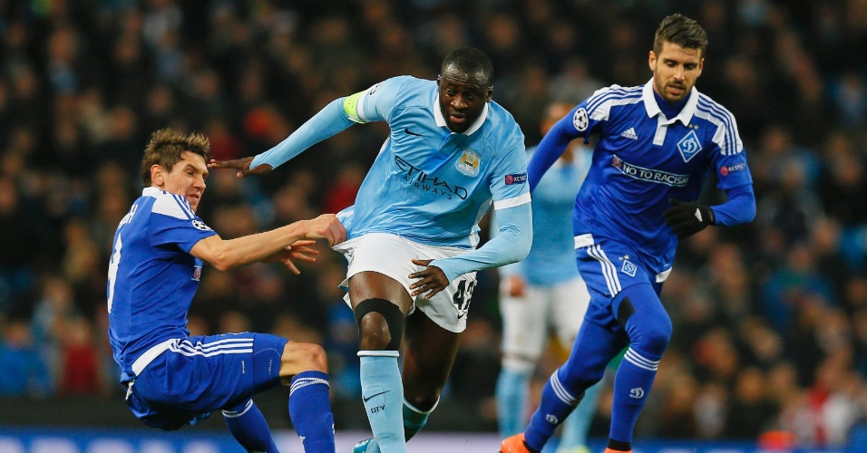 Yayá Touré avança com bola, apesar de estar sendo puxado por adversários