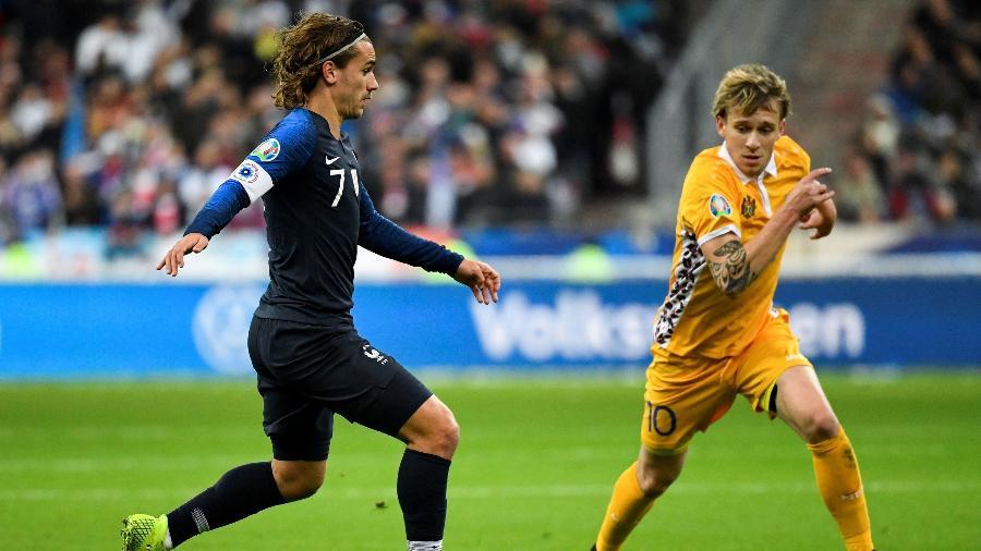 Antoine Griezmann, da França, em lance contra Eugeniu Cociuc, de Moldova, em jogo pelas Eliminatórias da Eurocopa -  Bertrand GUAY / AFP