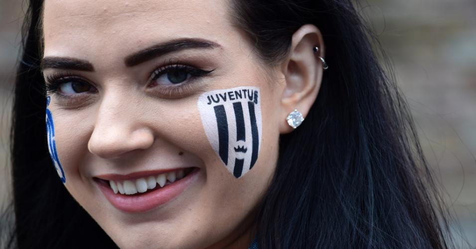 Torcedora pinta o rosto com os escudos de Real Madrid e Juventus antes da decisão em Cardiff