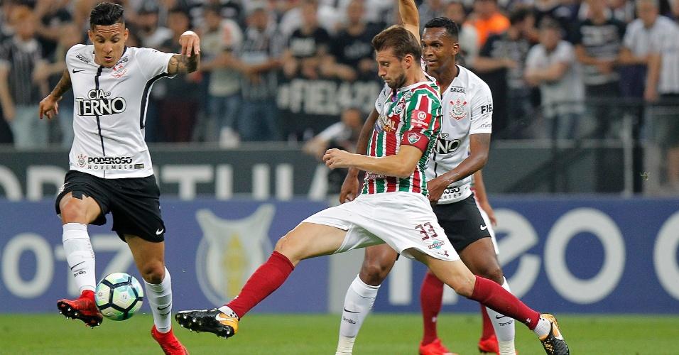 Guilherme Arana e Henrique disputam a bola na partida entre Corinthians e Fluminense, em Itaquera