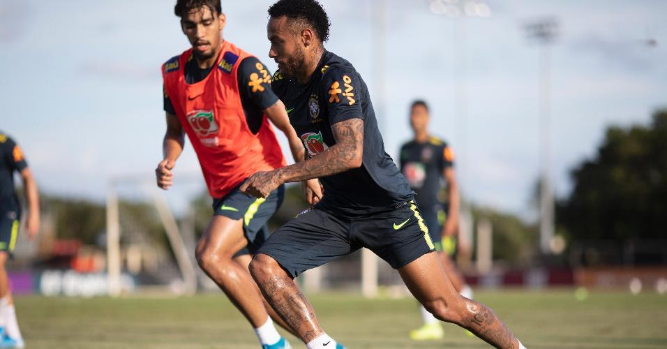 Neymar carrega a bola, observado por Lucas Paquetá