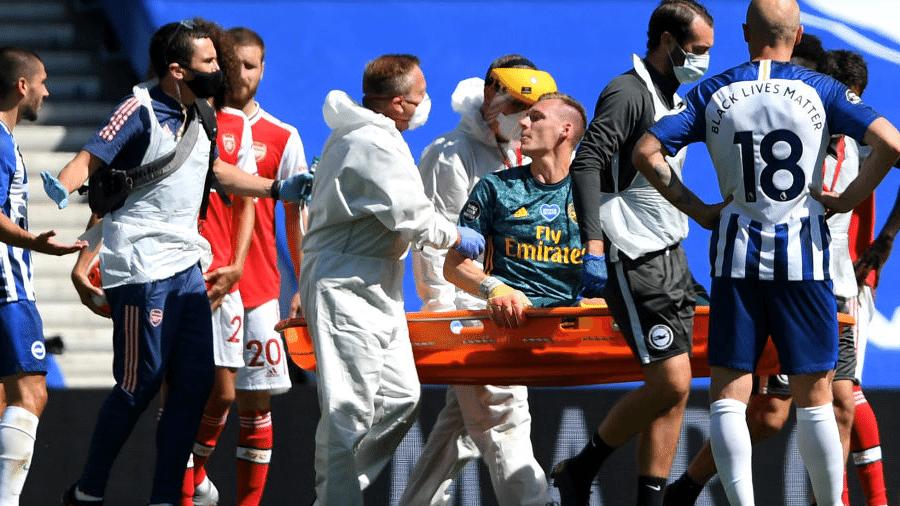 O goleiro do Arsenal, Bernd Leno, deixa o campo após sofrer uma lesão na perna - Reprodução