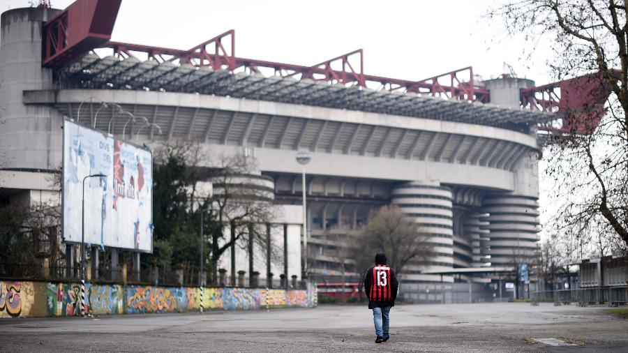 Torcedor do Milan caminha em frente ao estádio San Siro depois do jogo entre Milan e Genoa ser adiado devido ao coronavírus - Alberto Lingria/Xinhua