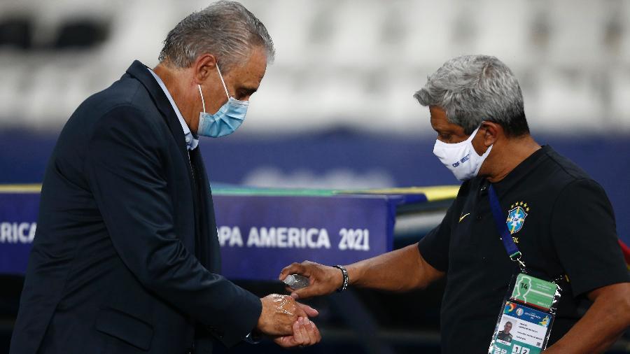 Funcionário da CBF passa álcool em gel nas mãos do técnico Tite antes de jogo da seleção brasileira - Wagner Meier/Getty Images