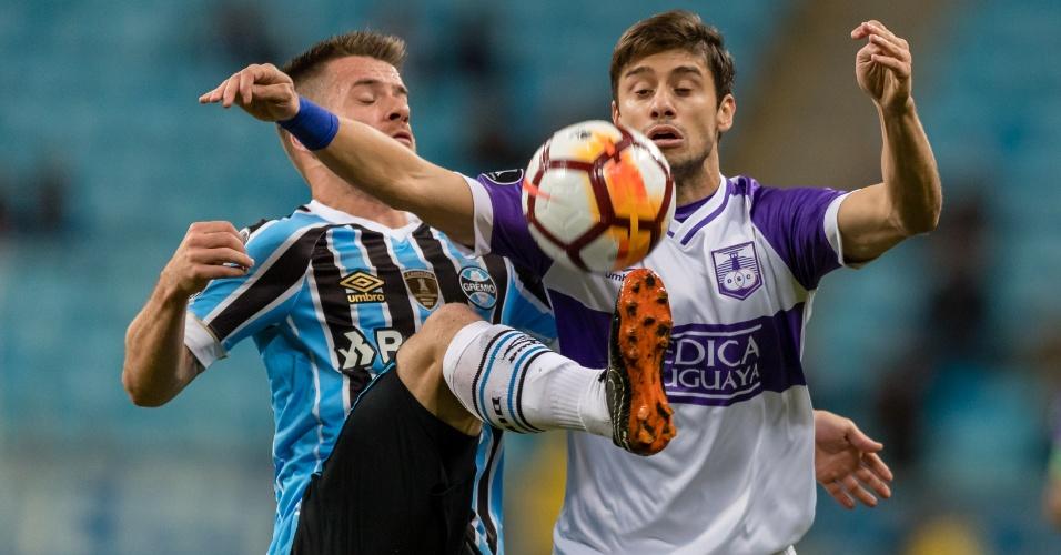 Ramiro disputa a bola com Maulella na partida entre Grêmio e Defensor, pela Libertadores