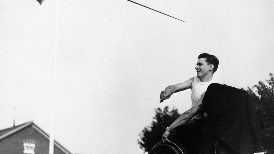 Ivor Elmes, um ex-policial palestino ferido em 1947, em sua cadeira de rodas enquanto lança um dardo nos Jogos de Stoke Mandeville, em 1953 - Bettmann Archive/Getty Images