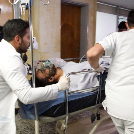 Alan Ruschel amparado por socorristas após o acidente - Guillermo Ossa/Reuters