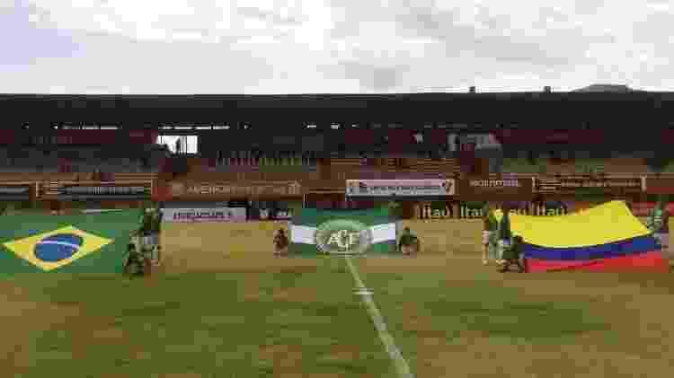 No gramado do Estádio Giulite Coutinho, no Rio de Janeiro, bandeiras do Brasil, da Colômbia e da Chapecoense são exibidas no gramado antes da partida Fluminense x Internacional - @FluminenseFC/Twitter - @FluminenseFC/Twitter