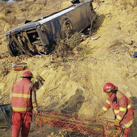 Bombeiros trabalham no resgate às vítimas de acidente de ônibus de torcedores do Barcelona de Guayaquil, em estrada no Peru - ZAPOTILLO TV / AFP