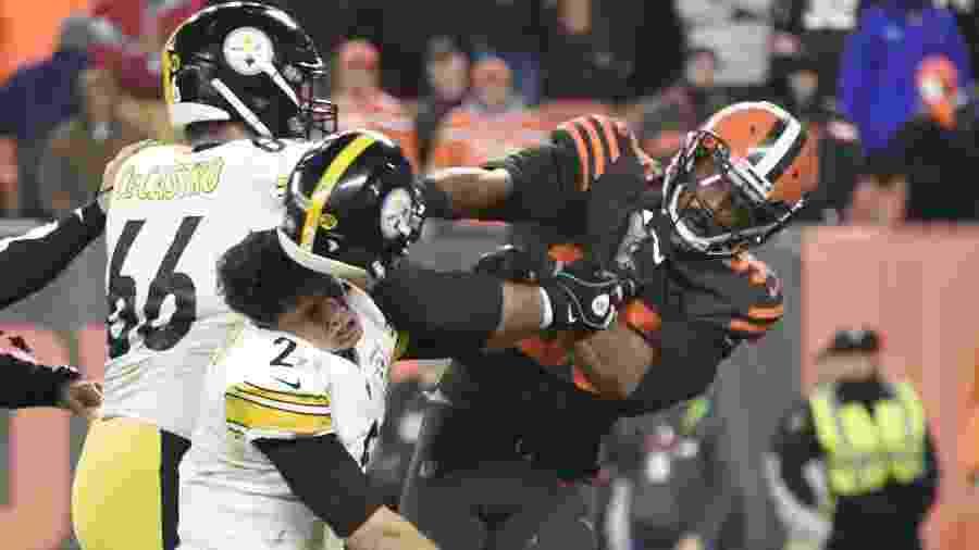 """Myles Garrett (à direita) dá uma """"capacetada"""" na cabeça de Mason Rudolph (à esquerda) durante confusão em jogo da NFL - Jason Miller/Getty Images/AFP"""