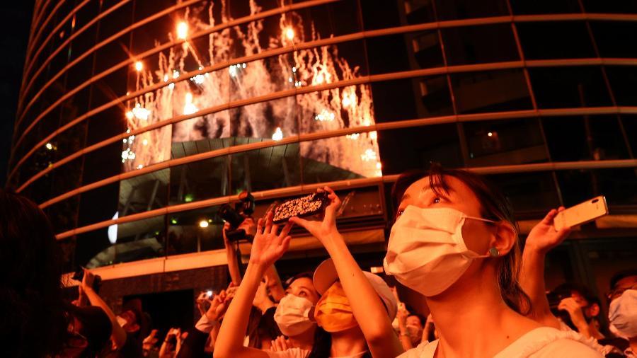 23.jul.2021 - Pessoas observam fora do estádio a queima de fogos da cerimônia de abertura da olimpíada de Tóquio - Issei Kato/Reuters