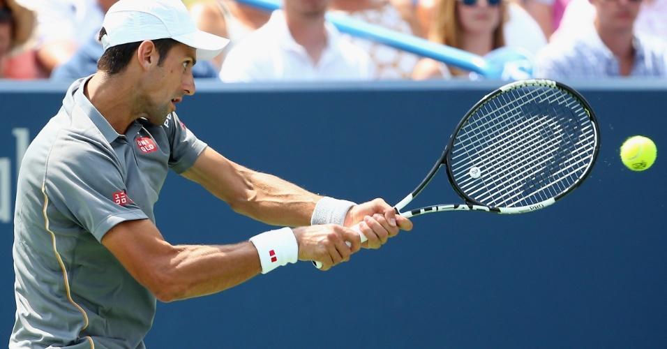 Djokovic se esforça para devolver uma bola de backhand contra Federer