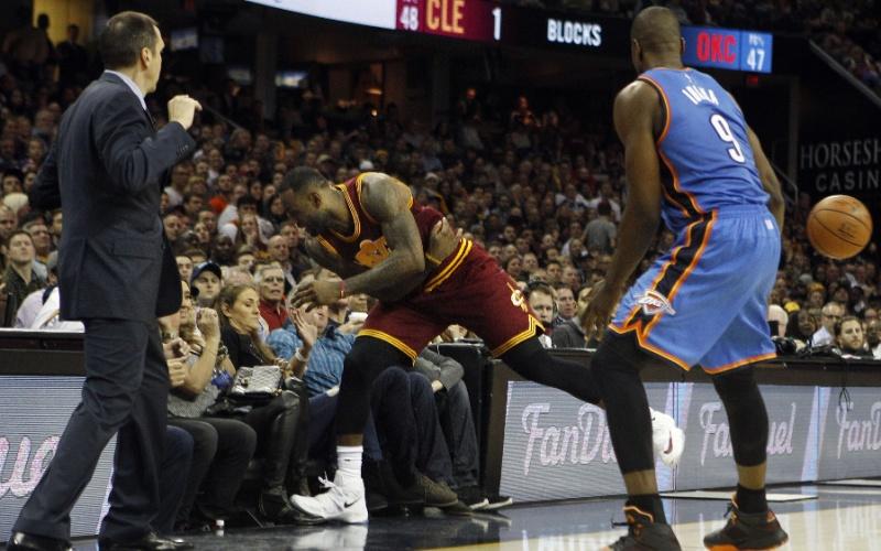 LeBron James salta para salvar uma bola, mas acaba se acidentando com torcedora
