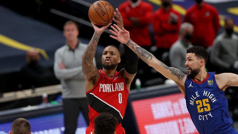 Damian Lillard tenta arremesso durante jogo do Portland TrailBlazers contra o Denver Nuggets nos playoffs da NBA - Matthew Stockman/Getty Images/AFP
