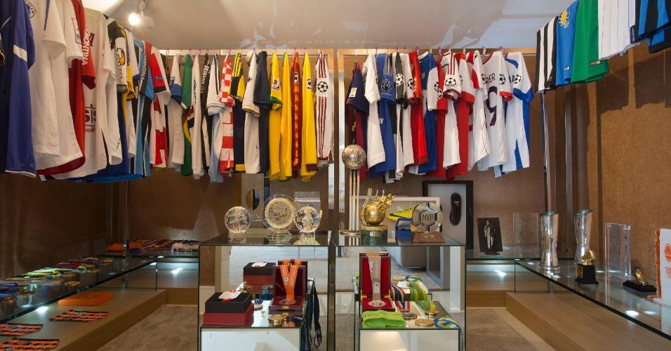 Sala de troféus da casa de Alex Teixeira tem lembranças importantes da carreira do jogador expostas como as camisas nas araras e as chuteiras. Medalhas e troféus estão dispostos em tótens no centro