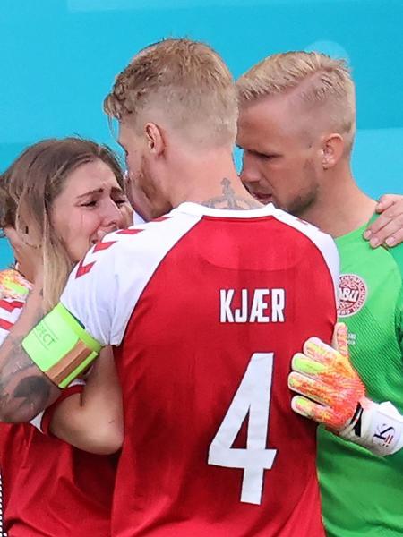 Goleiro da Dinamarca Kasper Schmeichel e zagueiro Simon Kjaer confortam Sabrina Kvist Jensen, namorada de Christian Eriksen - WOLFGANG RATTAY/AFP