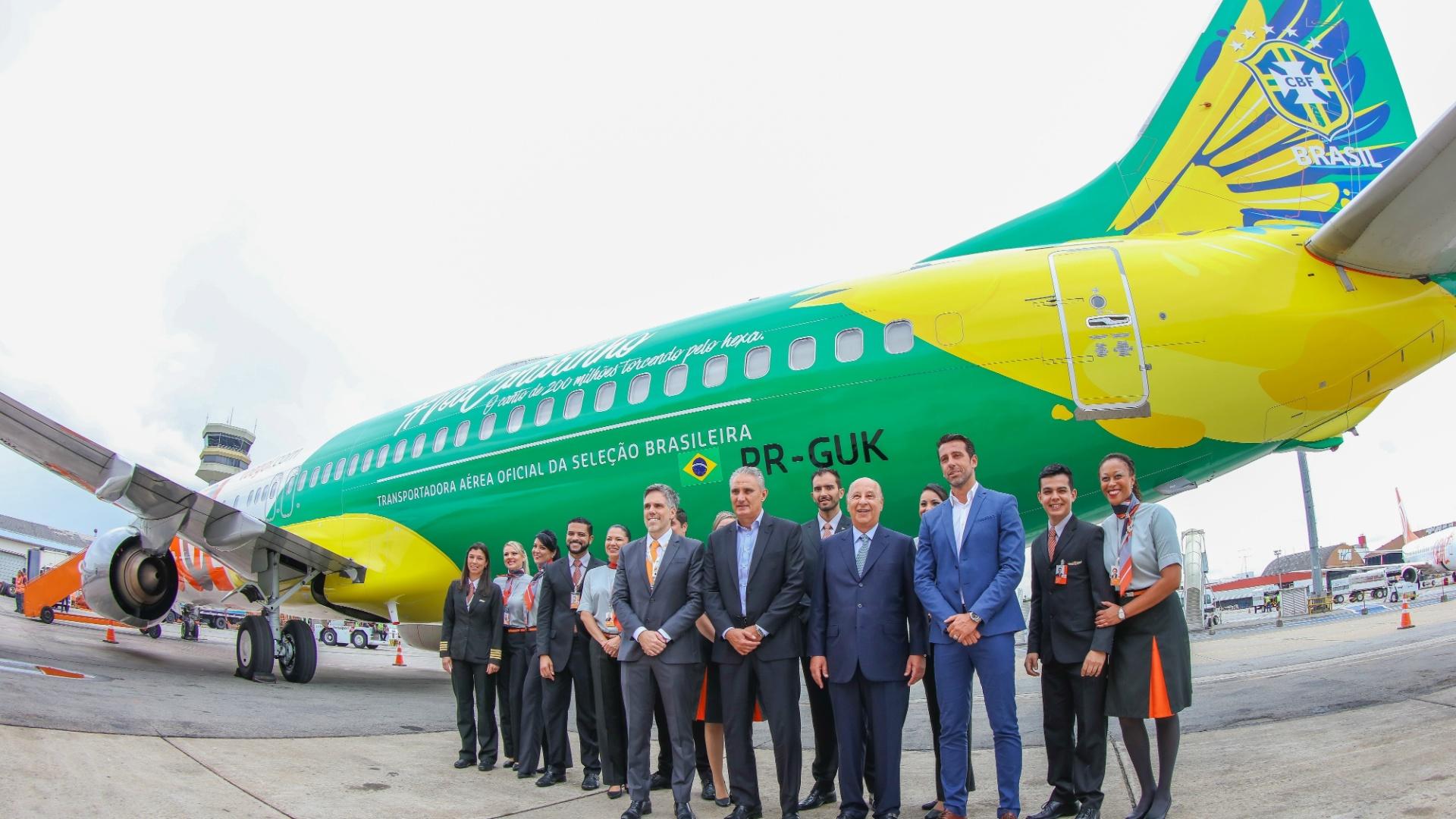 Tite, Marco Polo del Nero e Edu Gaspar posam em frente ao avião da seleção brasileira, fornecido pela Gol