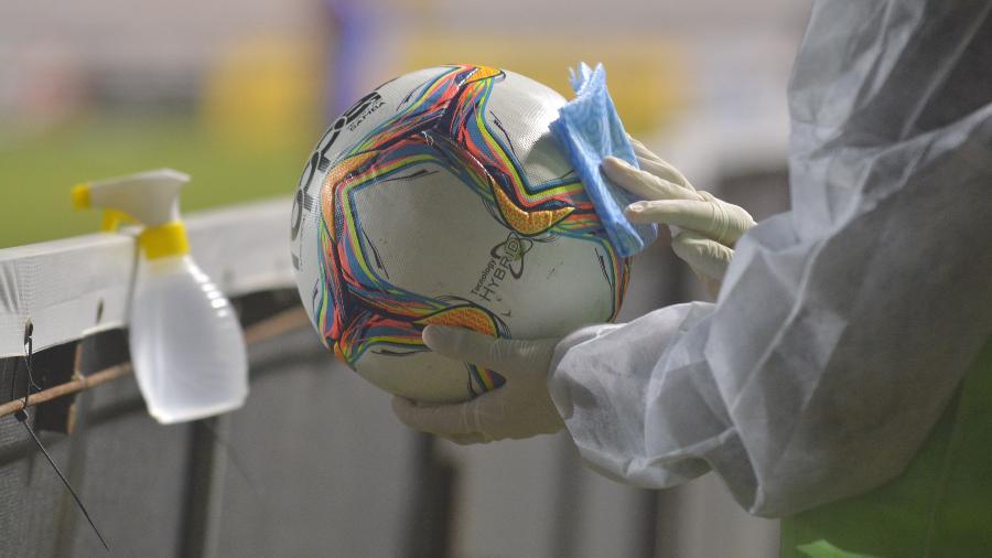 Gandula higieniza bola do Campeonato Catarinense durante partida entre Criciúma e Marcílio Dias, em julho de 2020 - Lucas Colombo/AGIF