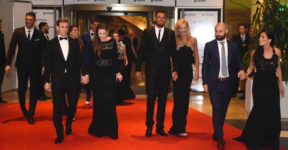 Os argentinos Lucas Biglia, Sergio Romero e Javier Mascherano e suas mulheres conversam após cerimônia de casamento de Messi