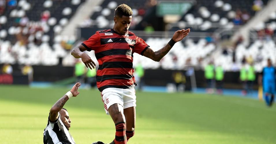 Bruno Henrique, do Flamengo, carrega a bola e leva carrinho de Alex Santana, do Botafogo