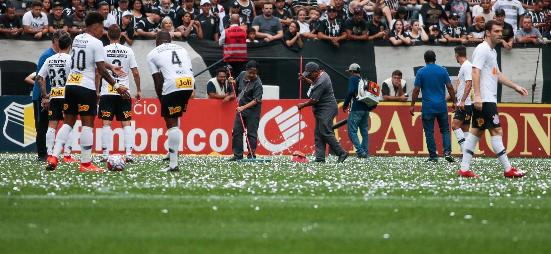 Funcionários limpam o gramado dos papeis laminados que atrasaram o início da partida na Arena Corinthians - Marcelo Zambrana/Agif