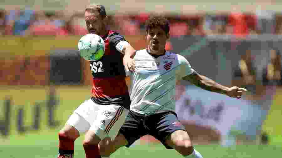 Everton Ribeiro e Marcio Azevedo disputam bola em jogo entre Flamengo e Athletico; calendário nacional está suspenso - Adriano Machado/Reuters