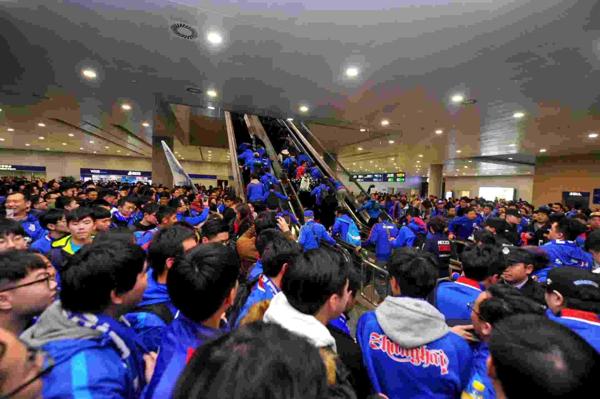 Centenas de torcedores comparecem ao aeroporto de Xangai para receber Tevez - AFP / STR / China