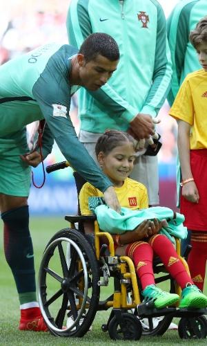 Cristiano Ronaldo entrega jaqueta para criança com deficiência física antes da partida entre Portugal e Rússia