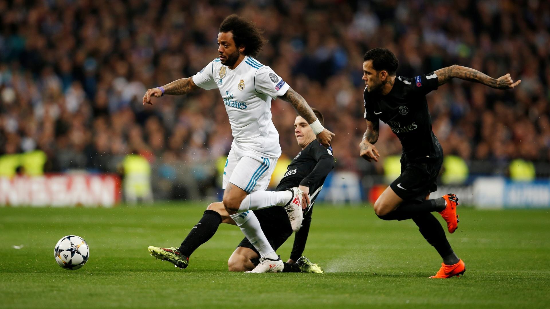 Marcelo e Daniel Alves disputam a bola no jogo entre Real e PSG