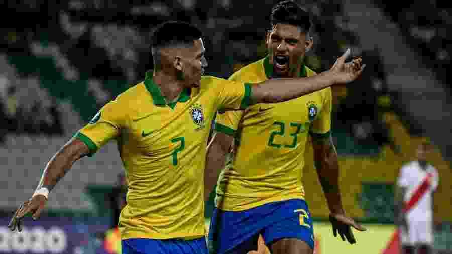 Paulinho (esq.) festeja gol contra o Peru pela estreia no Pré-Olímpico, ao lado de Yuri Alberto - Juan BARRETO / AFP