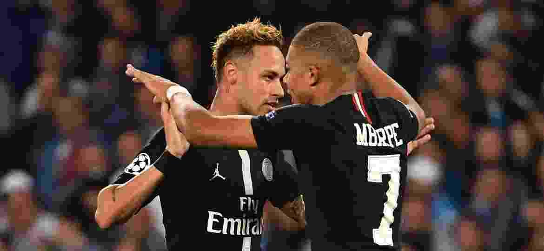 Neymar e Mbappé se abraçam durante jogo do PSG - Alberto PIZZOLI / AFP