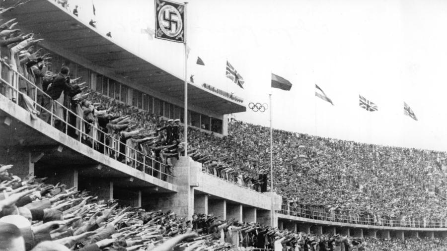 Pessoas presentes no Estádio Olímpico de Berlim fazem a saudação nazista durante a cerimônia de abertura dos Jogos Olímpicos de 1936 - Schirner Sportfoto/picture alliance via Getty Images